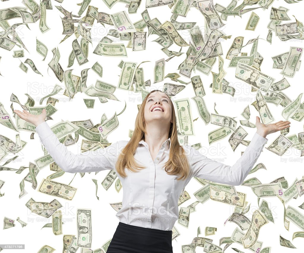 Beautiful blonde business woman is happy about flying dollar notes. stock photo