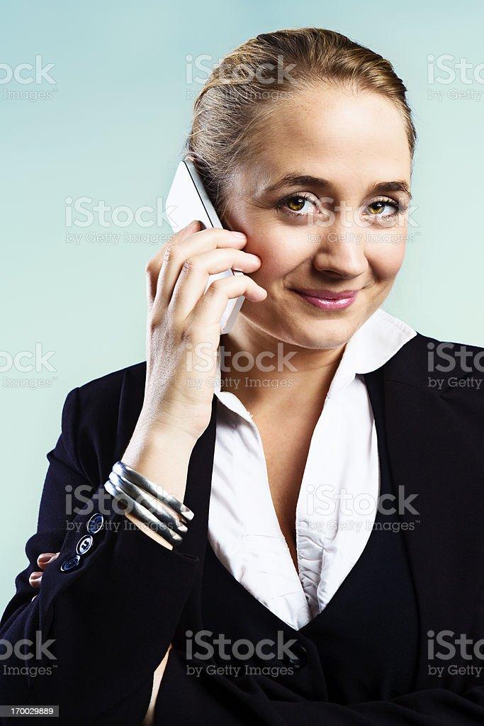 Beautiful blonde businesswoman talking on mobile phone stock photo