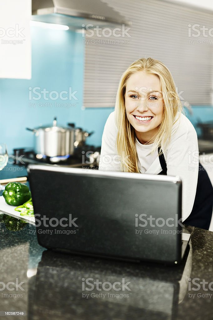 Beautiful blonde busy in kitchen checks her laptop royalty-free stock photo