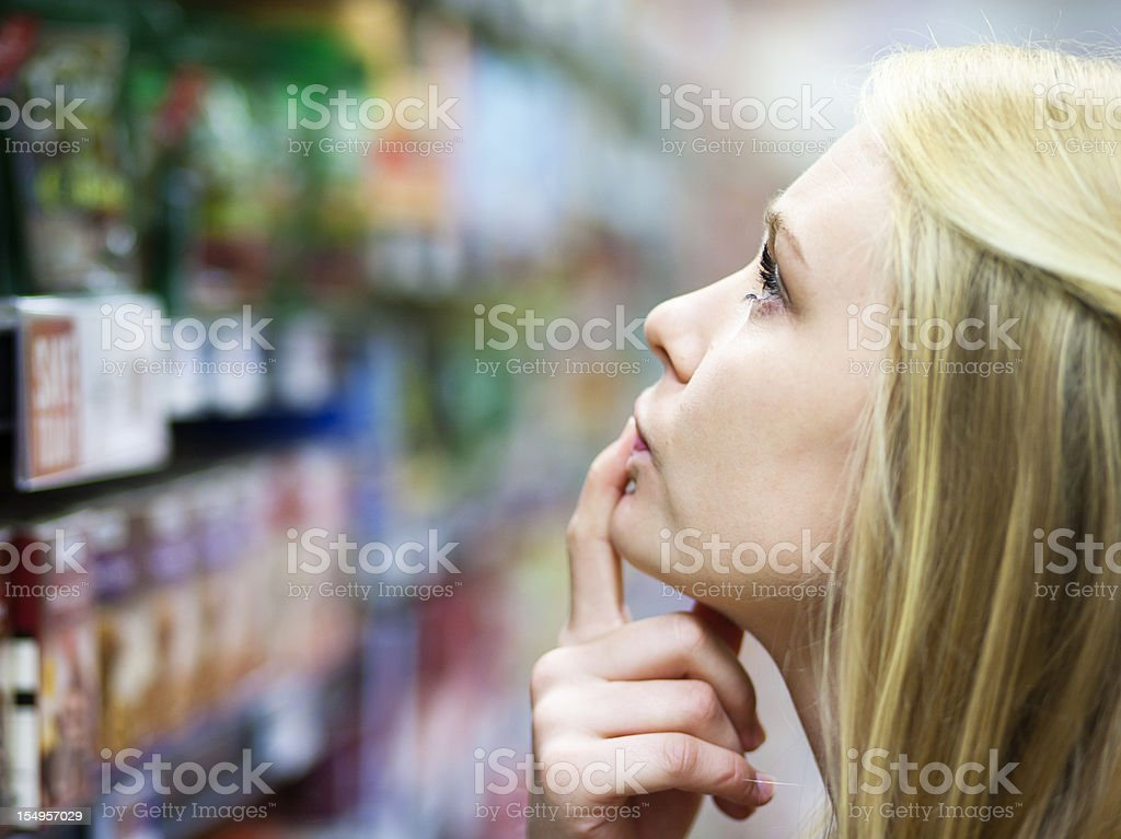 Beautiful blonde confused by wide choice of products in supermarket stock photo