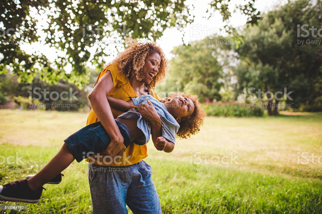 Beautiful blonde curly haired mother plays with her adorable bab stock photo