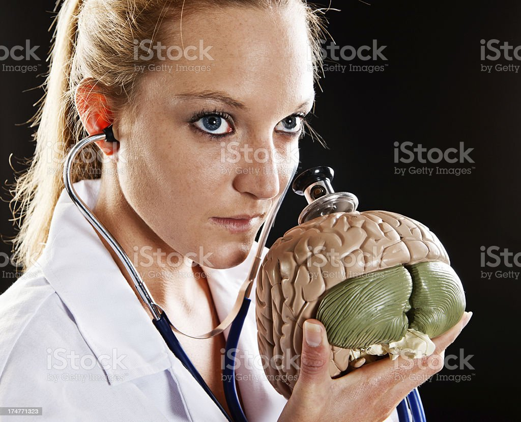 Beautiful blonde doctor examines model brain with stethoscope, looking serious stock photo
