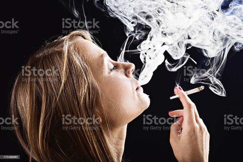 Beautiful blonde dreamily smoking hand-rolled marijuana joint stock photo