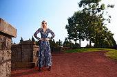 Beautiful Blonde Fashion Model In Blue Dress Near Stone Wall