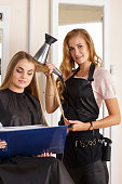 Beautiful blonde female hairdresser holding comb and hairdryer