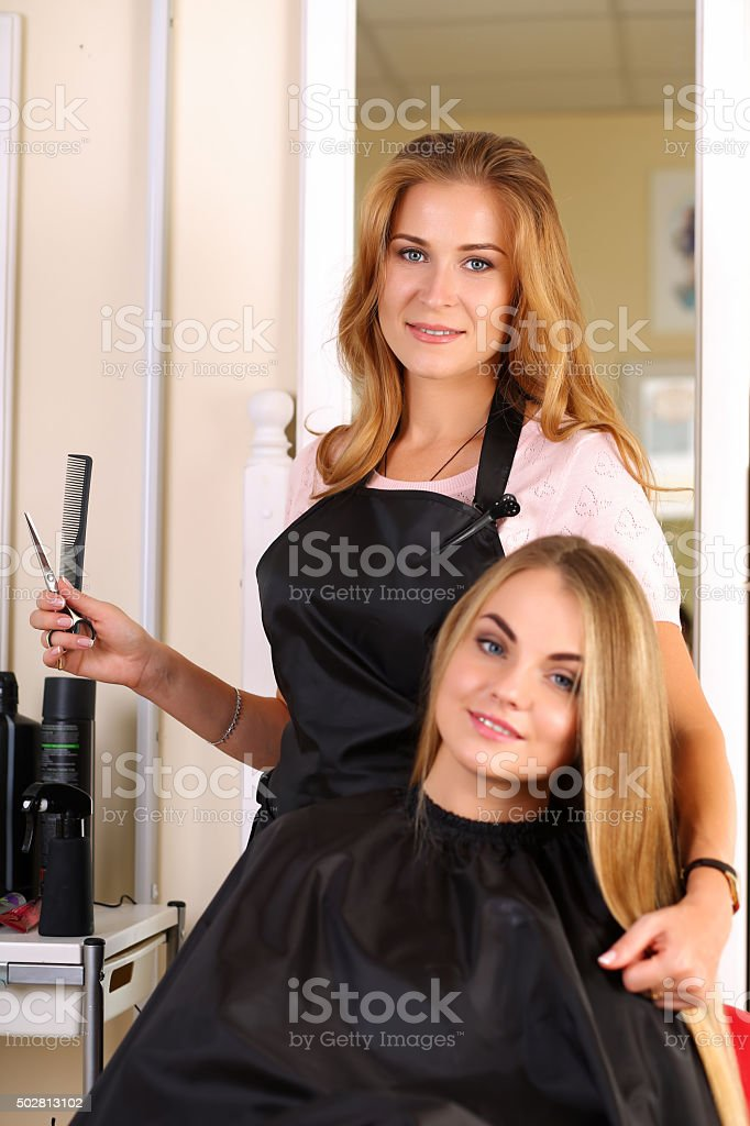 Beautiful blonde female hairdresser holding scissors and comb in stock photo