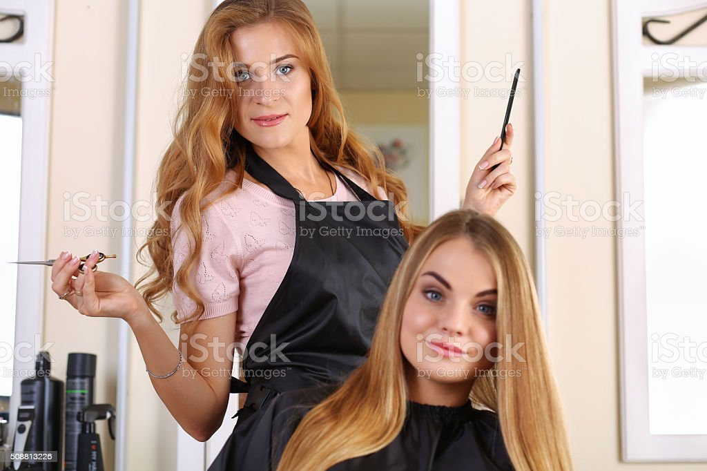 Beautiful blonde female hairdresser holding scissors stock photo