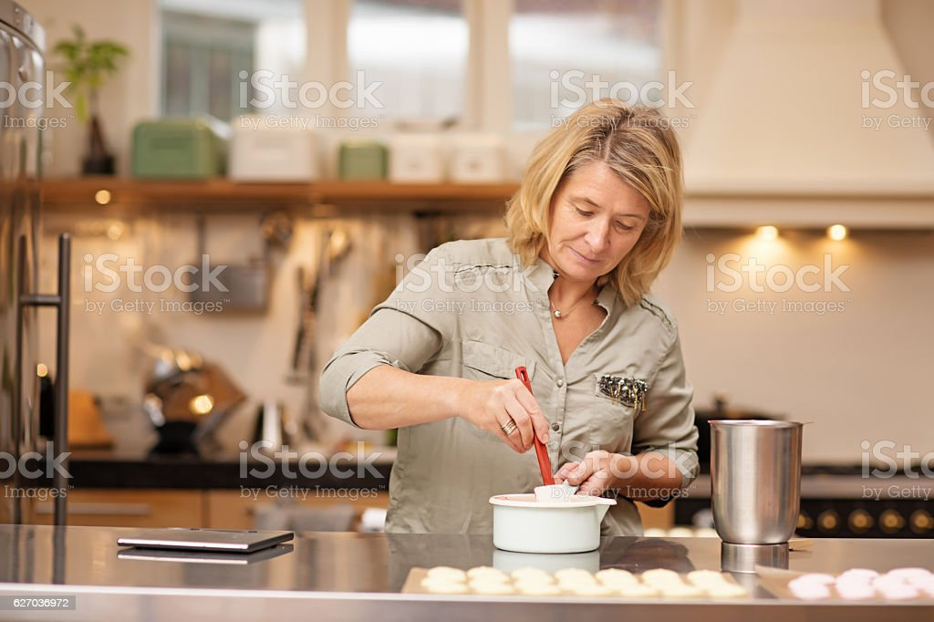 Beautiful blonde female woman baking sweets in stylish european kitchen stock photo