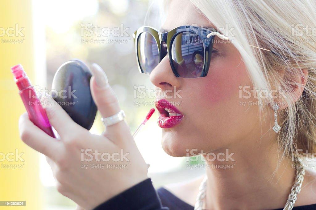 Beautiful blonde girl applying lip gloss over red lipstick stock photo