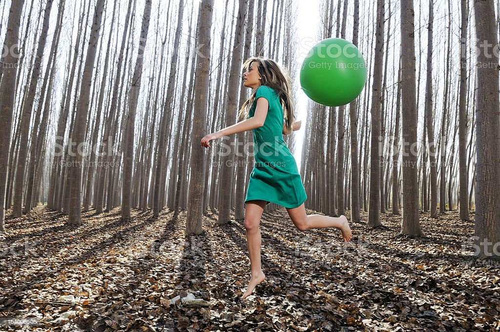 Beautiful blonde girl jumping into the woods with a balloon royalty-free stock photo
