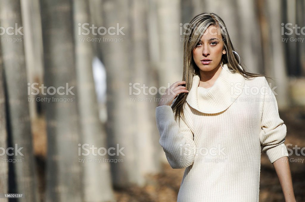 Beautiful blonde girl standing in a poplar forest stock photo