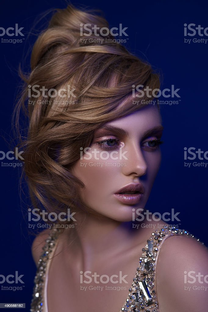 Beautiful blonde girl with unusual hairstyle and glamorous make-up stock photo
