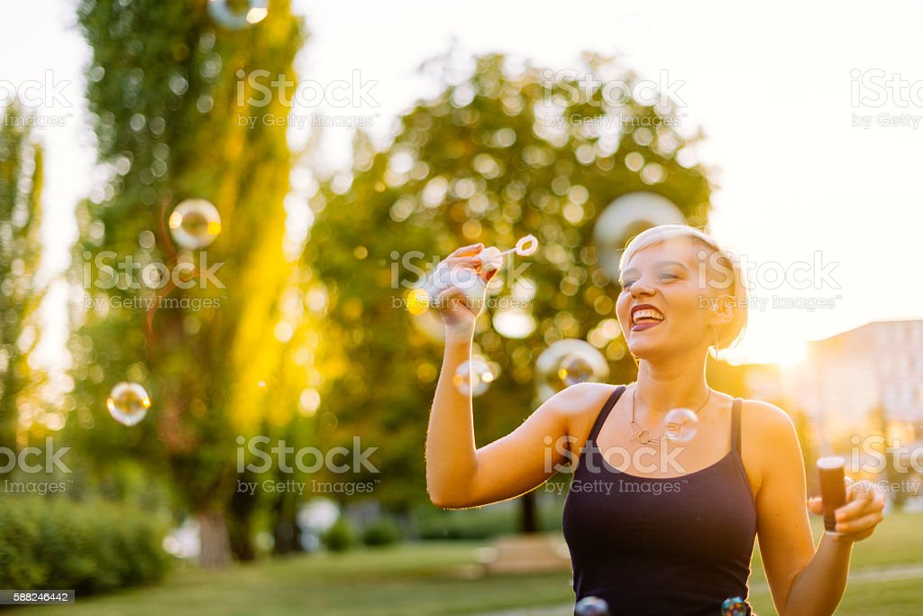 Beautiful blonde hipster blowing bubbles in park stock photo