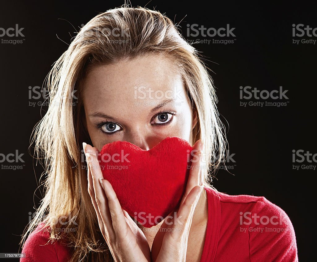 Beautiful blonde holds red velvet heart: romance in the air stock photo
