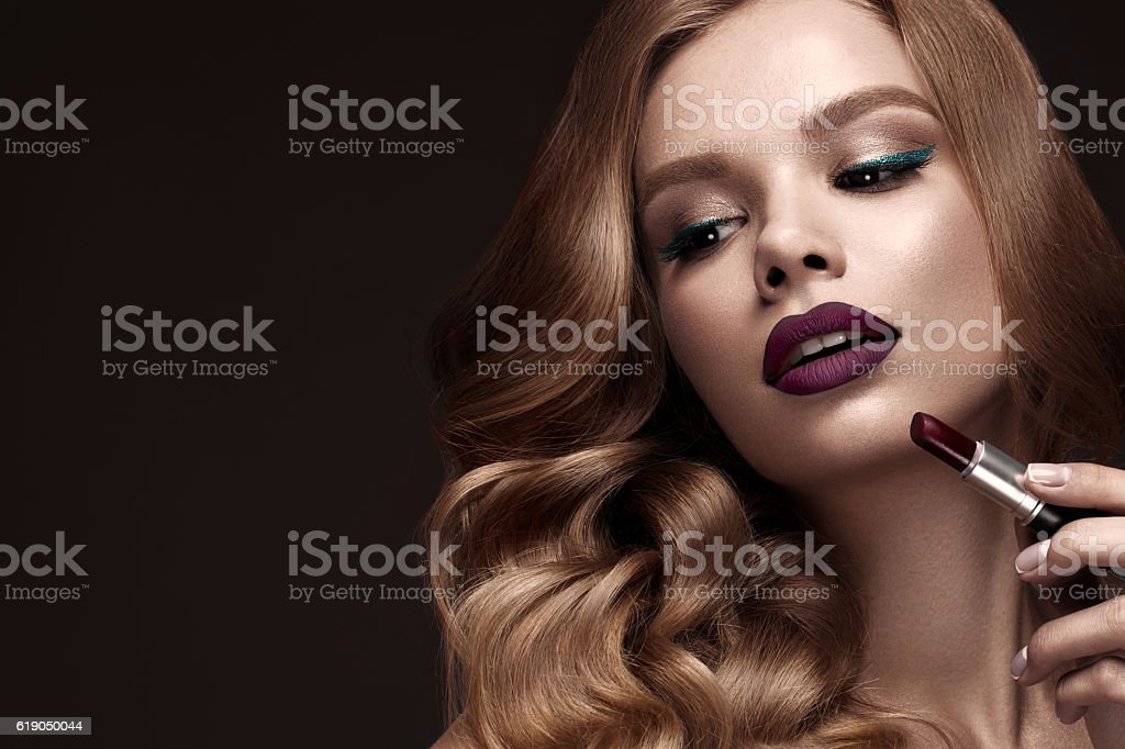 Beautiful blonde in a Hollywood manner with curls, dark lips stock photo