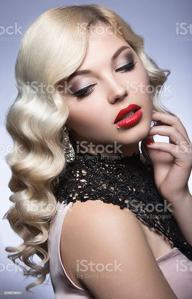 Beautiful blonde in Hollywood manner with curls and red lips stock photo