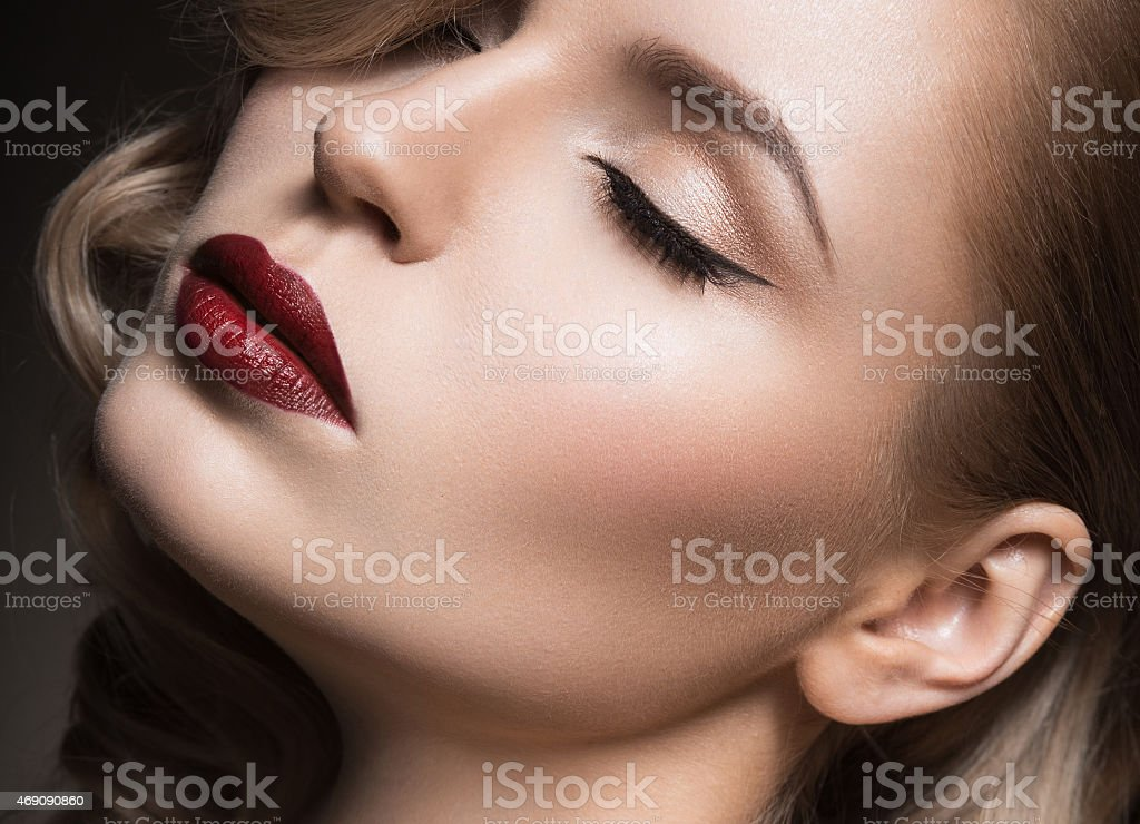 Beautiful blonde in Hollywood manner with curls, red lips. stock photo