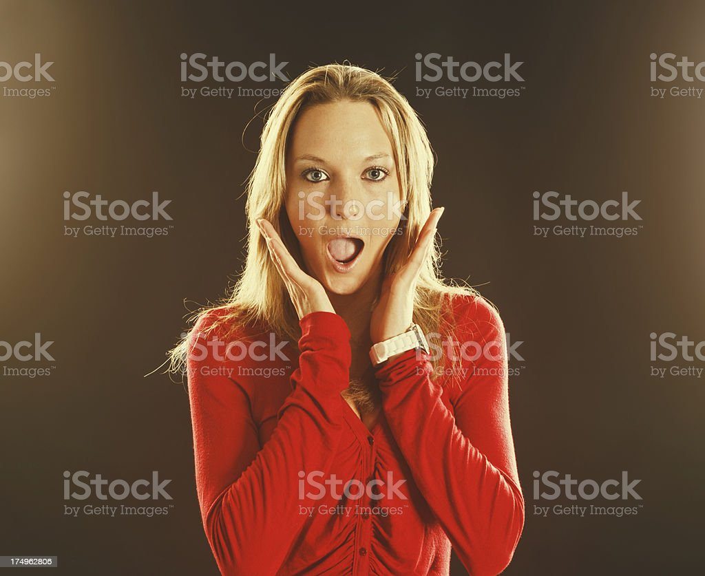 Beautiful blonde in red gets lovely surprise! stock photo