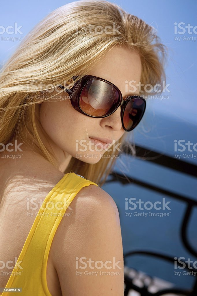 Beautiful blonde in the yellow dress at blue sky. stock photo