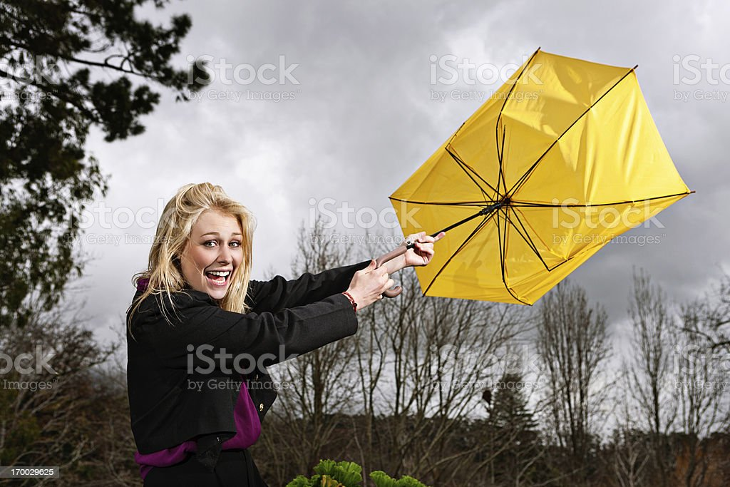 Beautiful blonde laughs as wind blows umbrella inside out stock photo