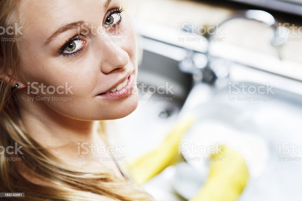 Beautiful blonde looks up from doing the dishes, smiling royalty-free stock photo
