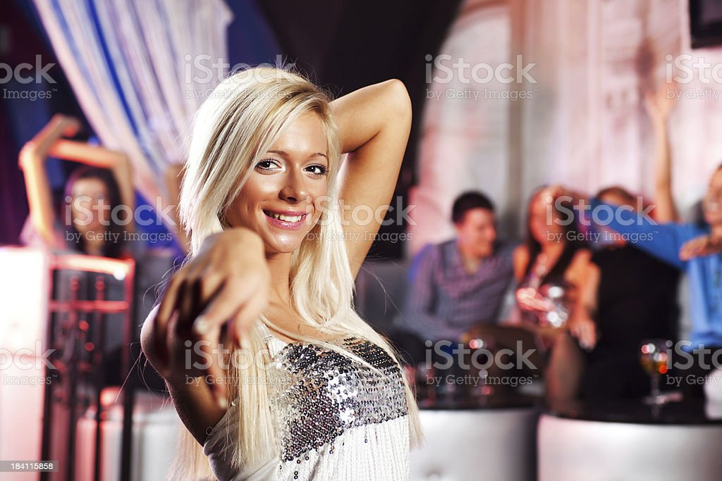 Beautiful blonde pointing finger at the camera in disco club royalty-free stock photo