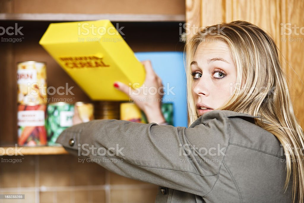 Beautiful blonde reaches for cereal in kitchen cabinet stock photo