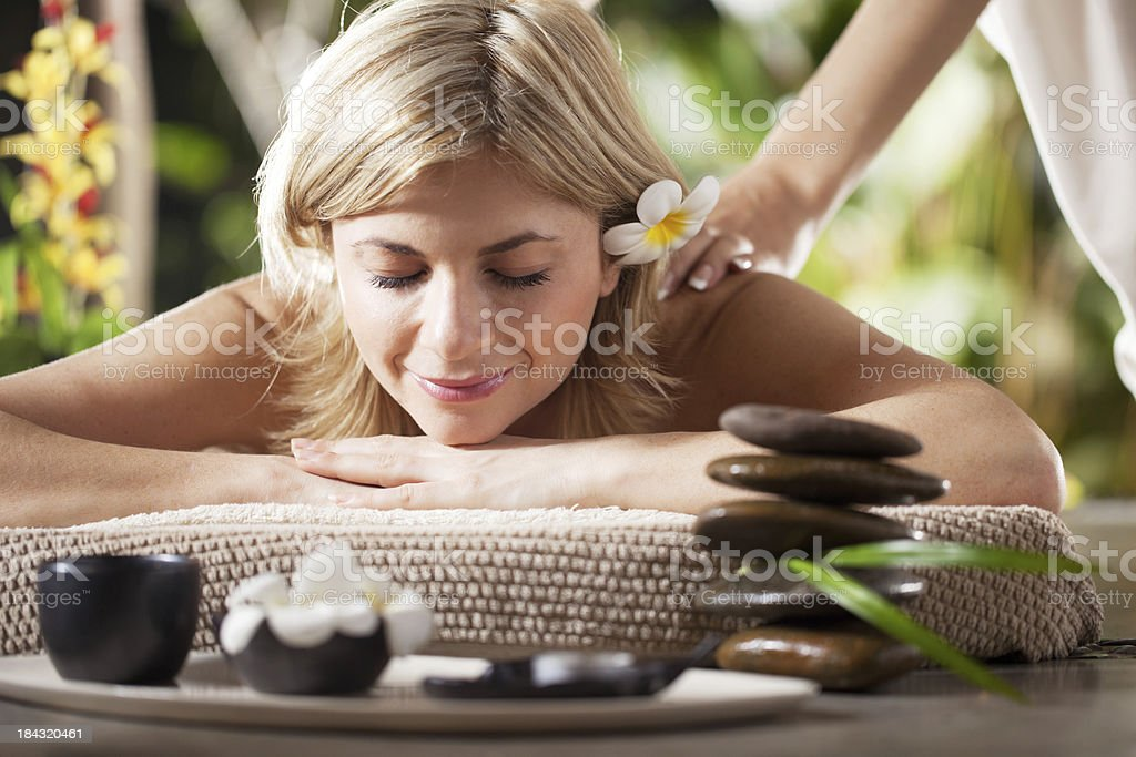 Beautiful blonde receiving back massage in spa center royalty-free stock photo