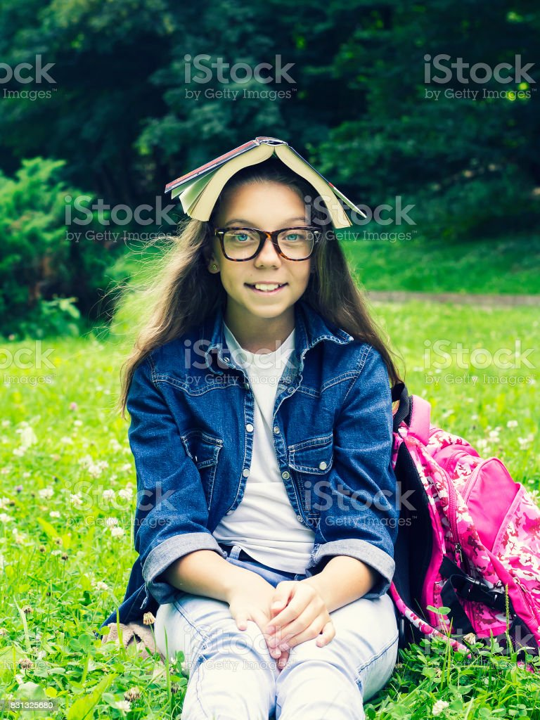 Beautiful blonde schoolgirl girl in jeans shirt reading a book on grass with a backpack in the park stock photo
