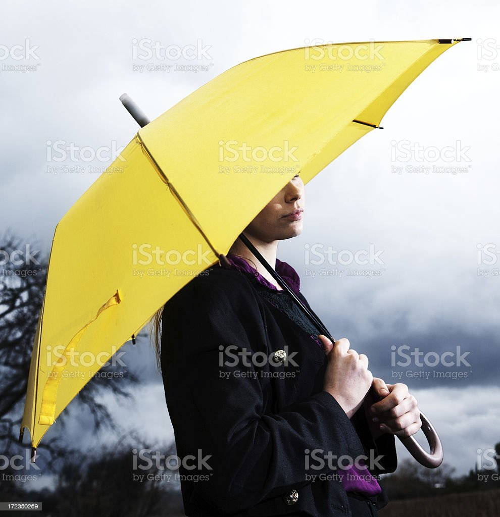 Beautiful blonde sheltering under umbrella in thunderstorm royalty-free stock photo
