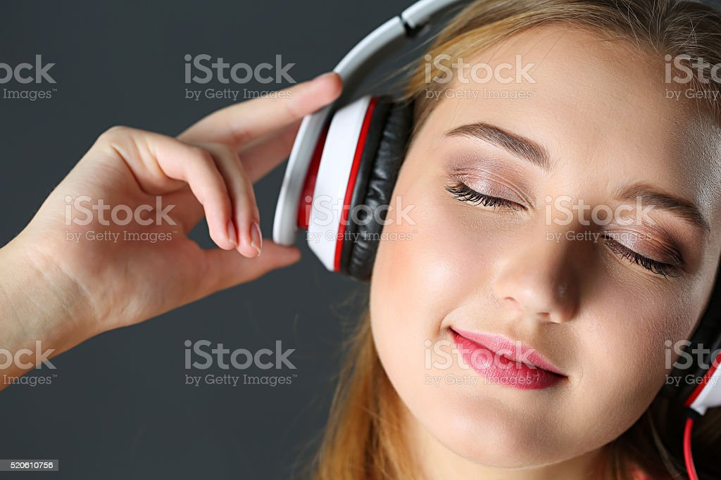 Beautiful blonde smiling woman with eyes closed wearing headphon stock photo