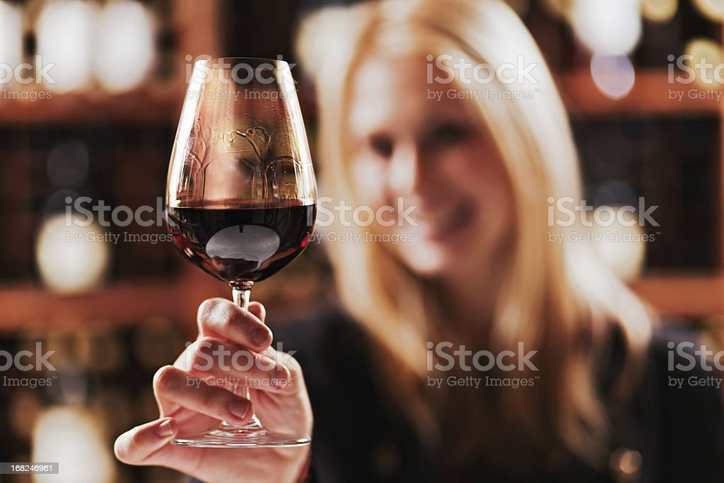 Beautiful blonde tasting red wine in a winery cellar royalty-free stock photo