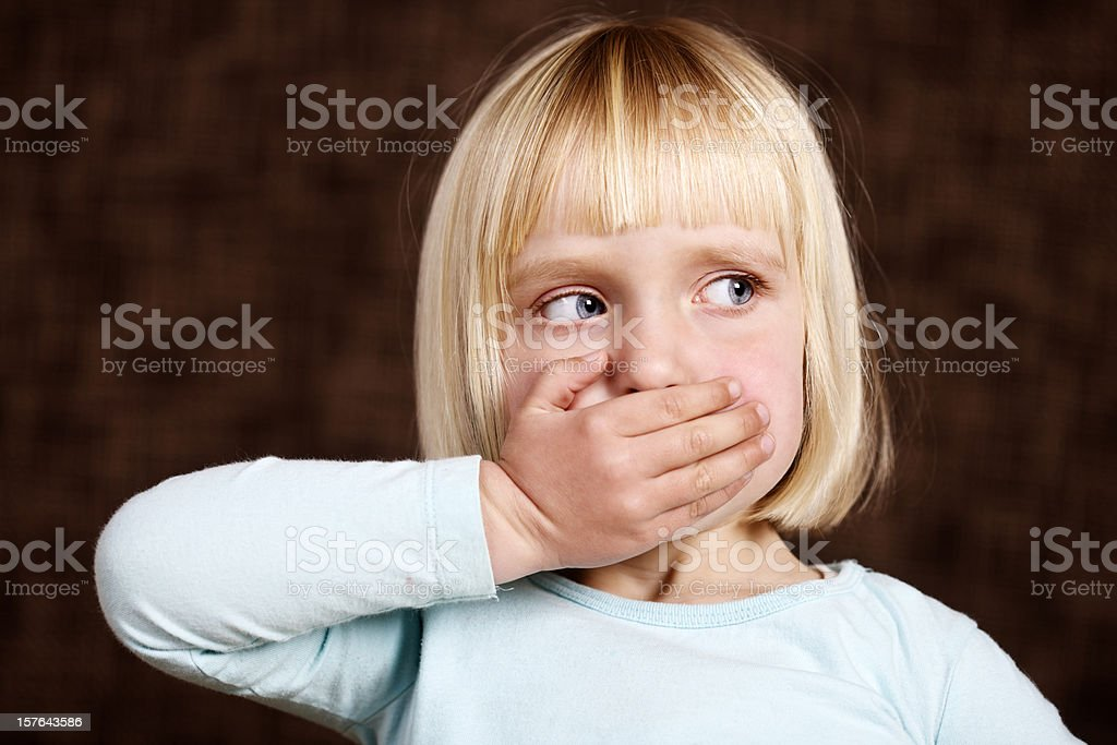 Beautiful blonde toddler makes 'Speak no Evil' sign stock photo
