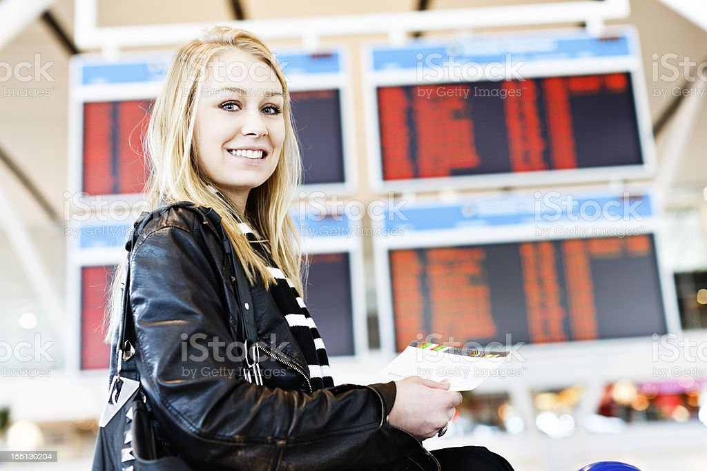 Beautiful blonde traveler smiles, holding her boarding pass in airport royalty-free stock photo