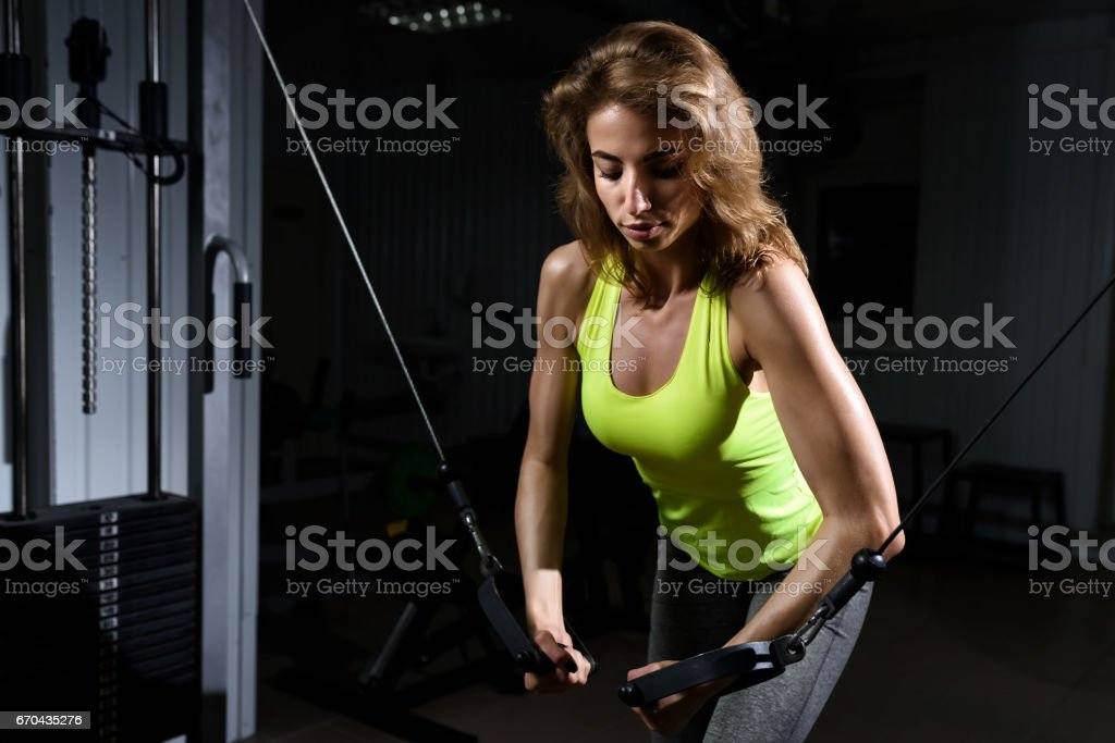 Beautiful blonde using pulleys to tone her muscles at the gym stock photo