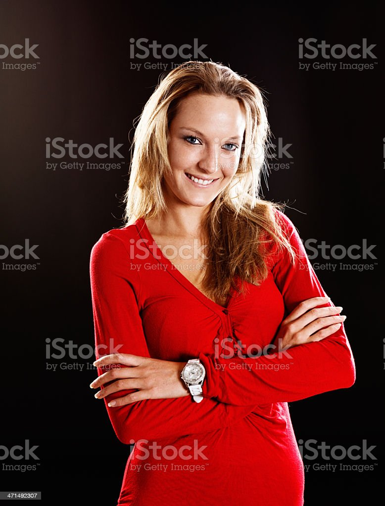 Beautiful blonde wearing red smiles confidently with folded arms stock photo