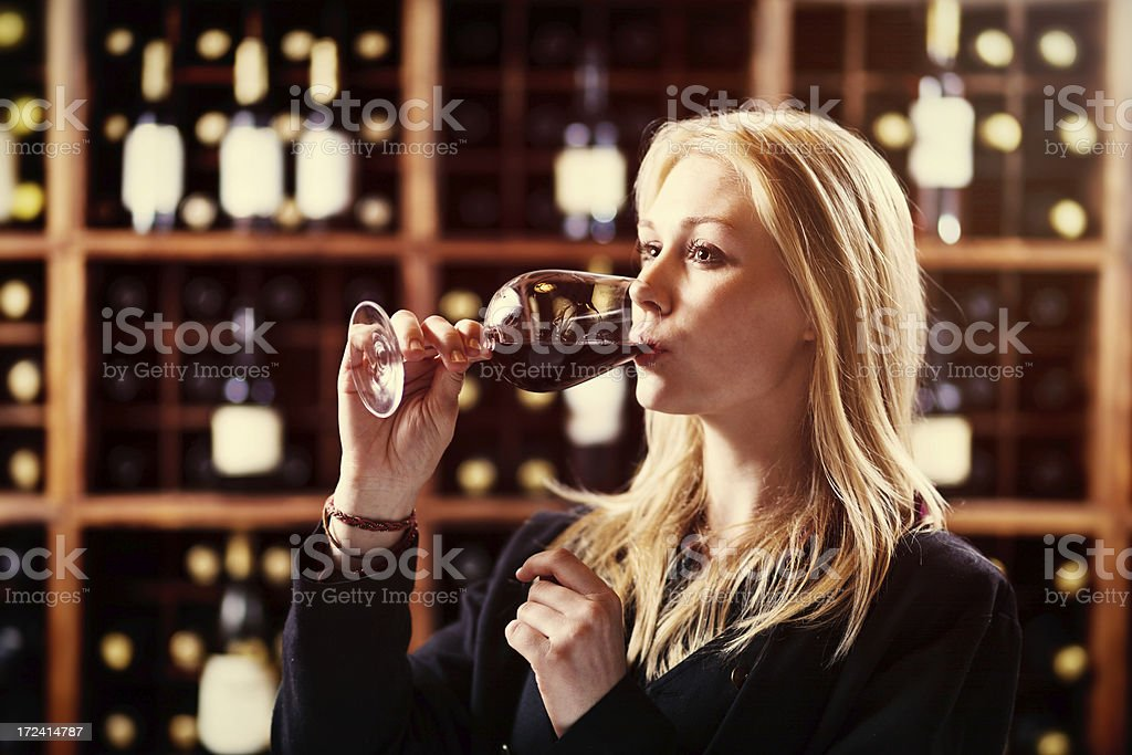 Beautiful blonde wine taster sipping Merlot in winery cellar royalty-free stock photo