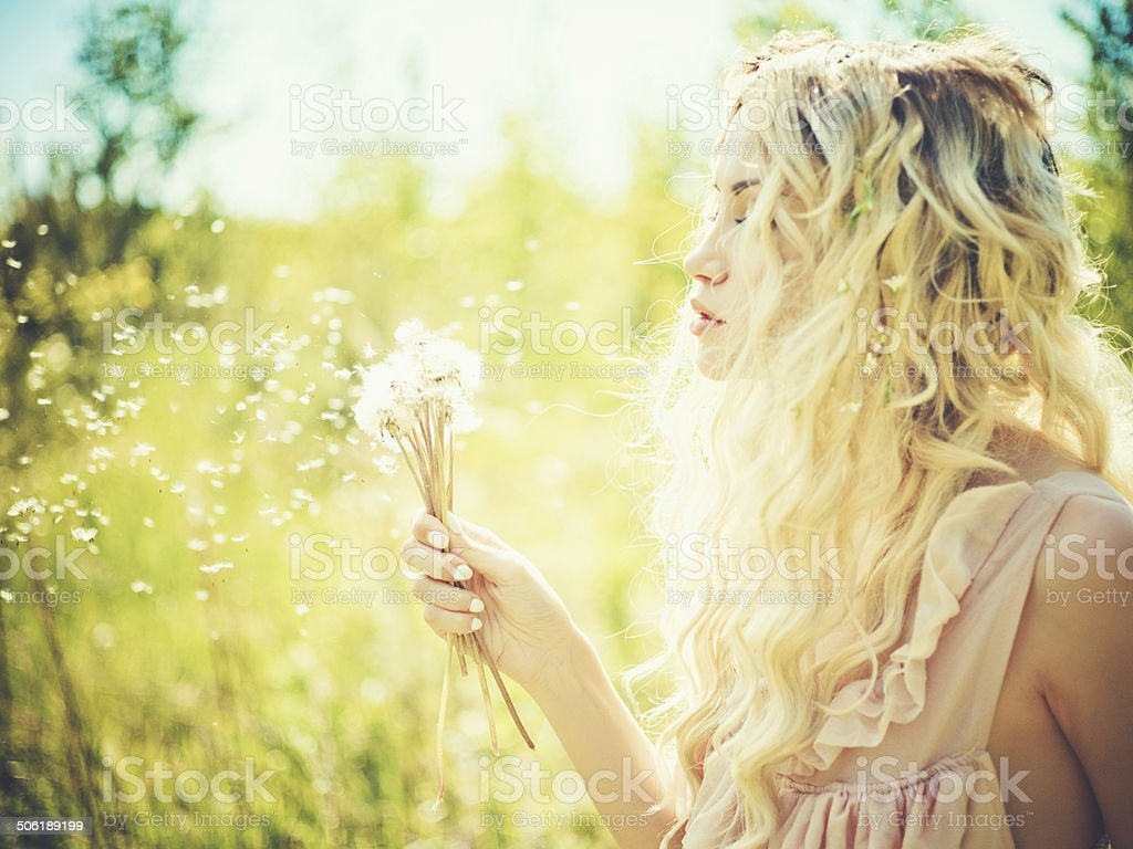 Beautiful blonde with dandelions stock photo