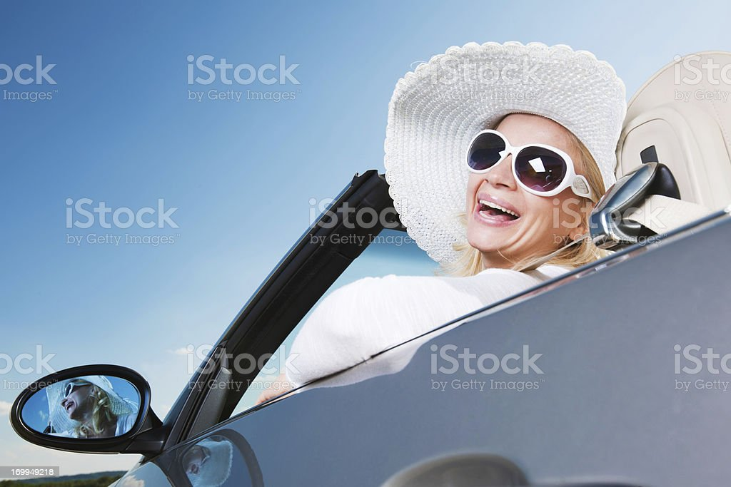 Beautiful blonde with hat and sunglasses driving cabriolet car. royalty-free stock photo