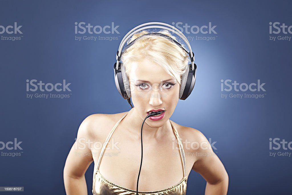 Beautiful blonde with headphones on blue background royalty-free stock photo