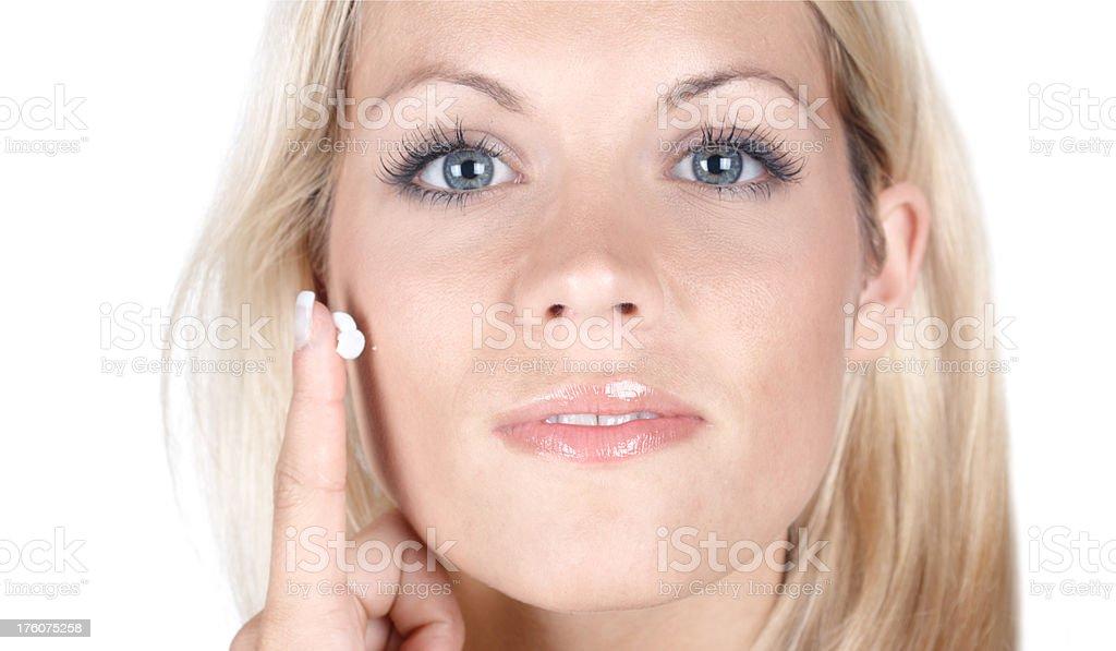 beautiful blonde woman applying cream stock photo