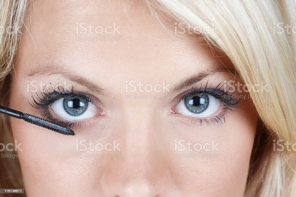 beautiful blonde woman brushing her eyelash stock photo