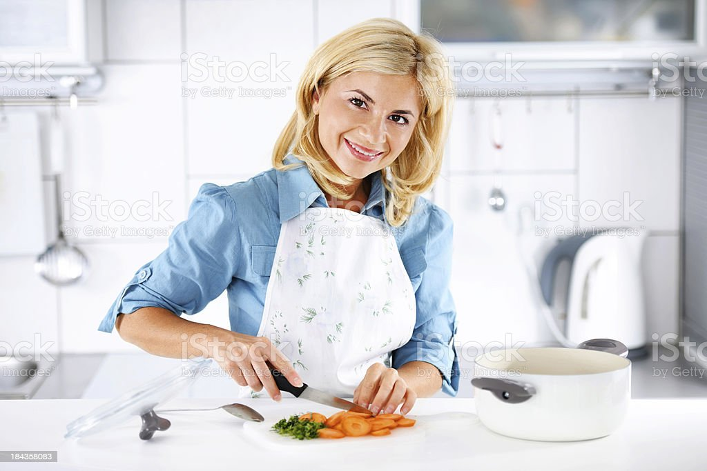 Beautiful blonde woman cooking in the kitchen. royalty-free stock photo