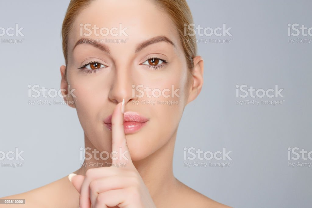 Beautiful blonde woman finger on lips Beauty Headshot Woman looking at camera stock photo