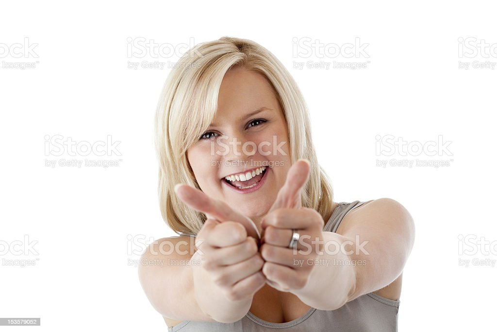Beautiful blonde woman holds both thumbs up and smiles royalty-free stock photo