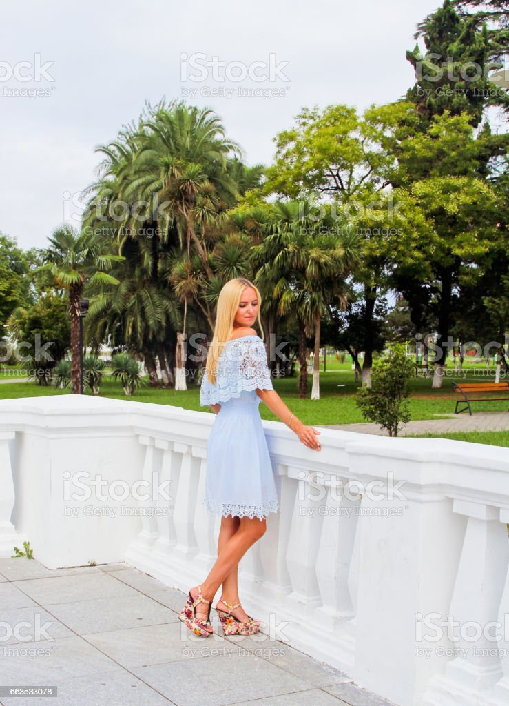 Beautiful blonde woman in blue dress posing in tropical park stock photo