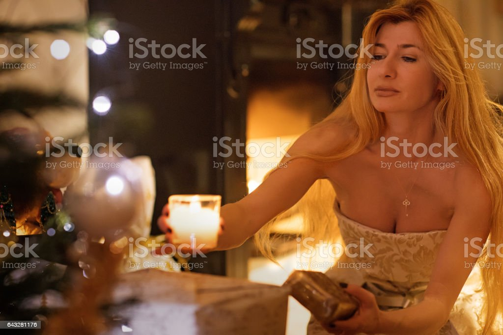 Beautiful blonde woman in christmas scene with festive decorations in indoor setting stock photo