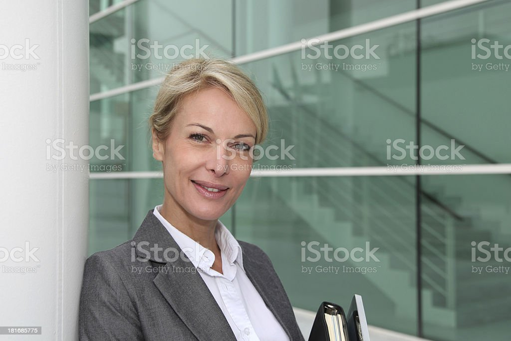 Beautiful blonde woman leaning on wall of building royalty-free stock photo
