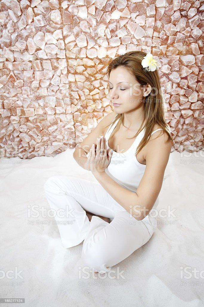Beautiful blonde woman meditating in salt room. stock photo