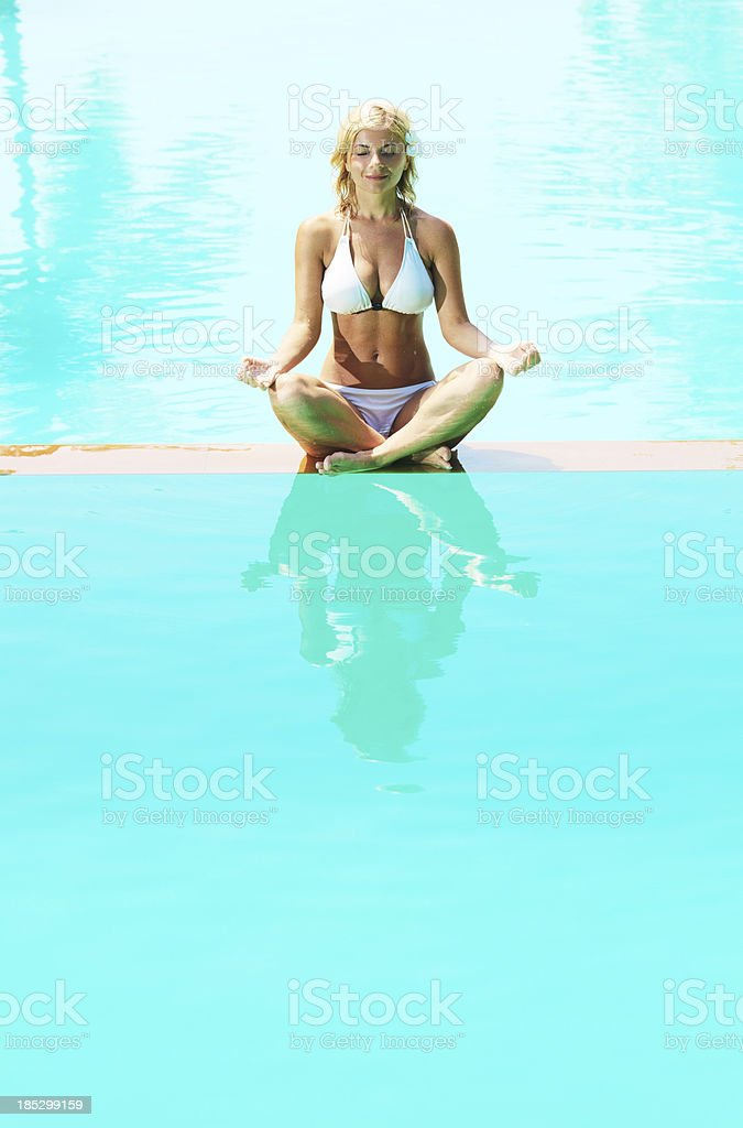 Beautiful blonde woman meditating on the edge of swimming pool. royalty-free stock photo